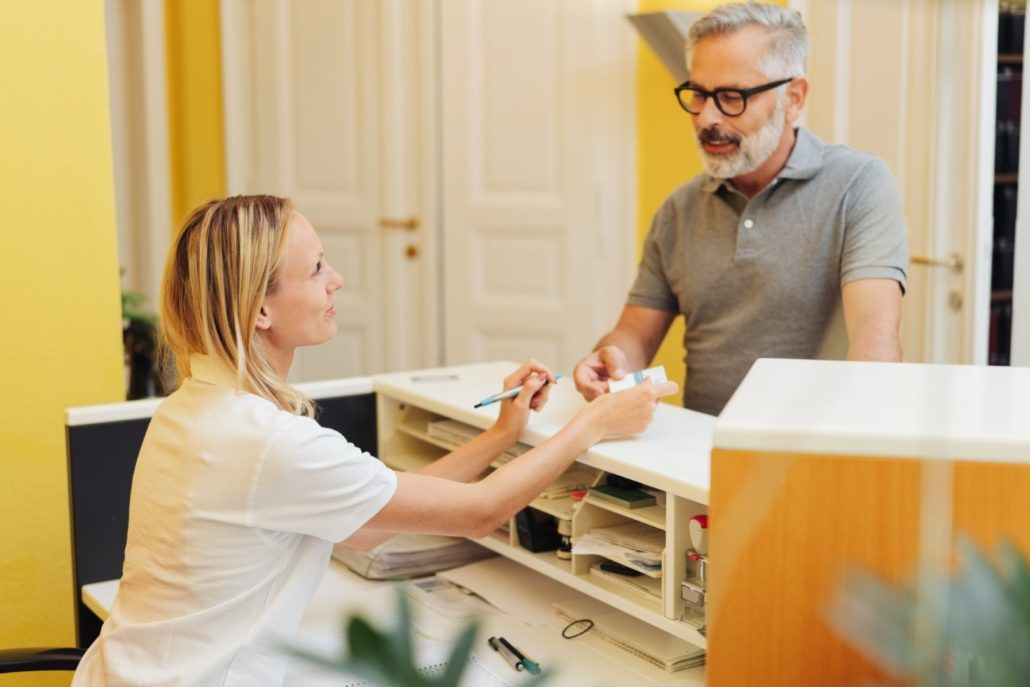 Man providing health insurance information to medical receptionist in Georgia